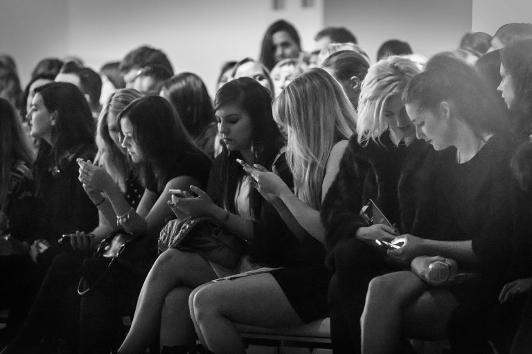 London Fashion Week audience checking cellphones mobiles