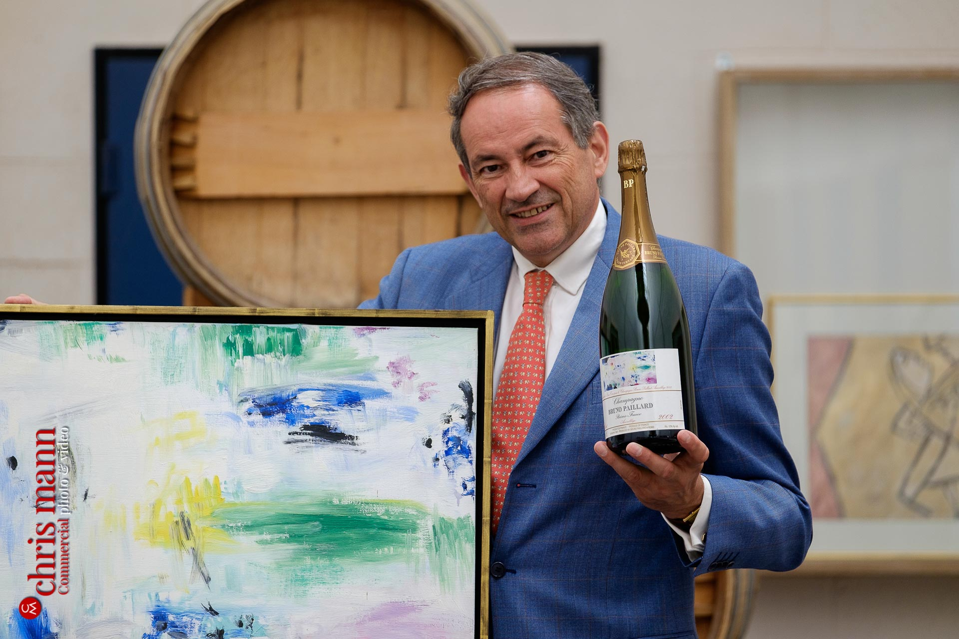 Bruno Paillard with a bottle of his champagne and the original painting that apperas on its label