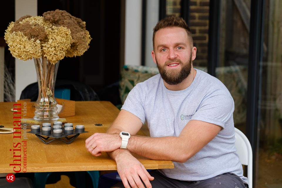 Guildford craftsman portraits - handyman Will Lingard seated at a wooden table
