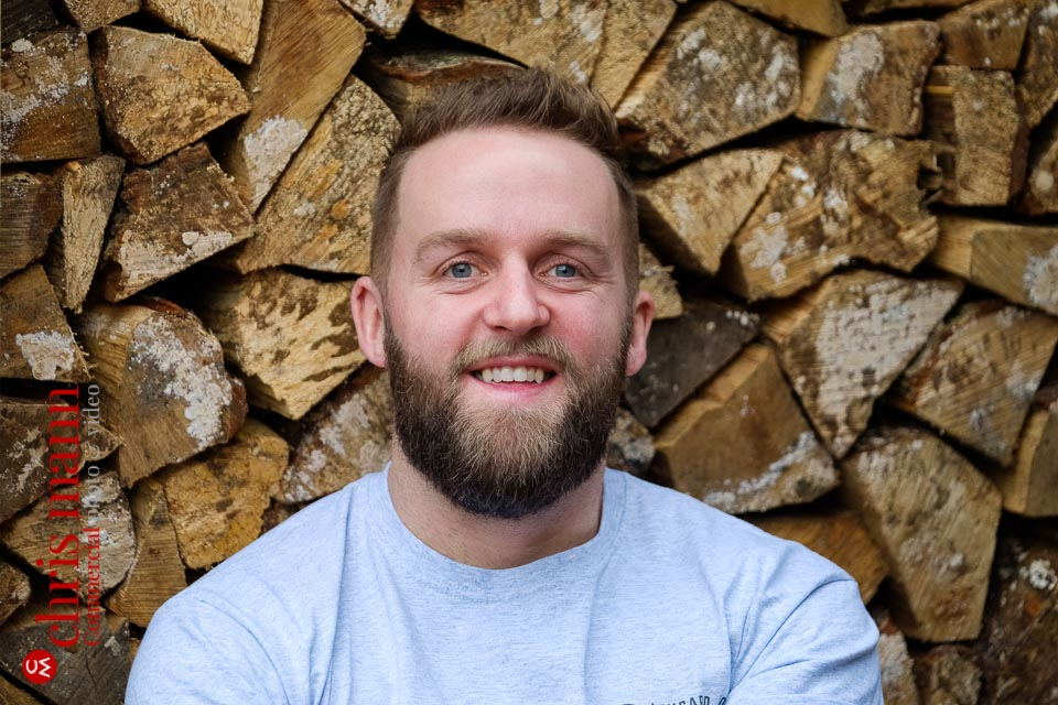 Guildford craftsman portraits - handyman Will Lingard with a woodpile background